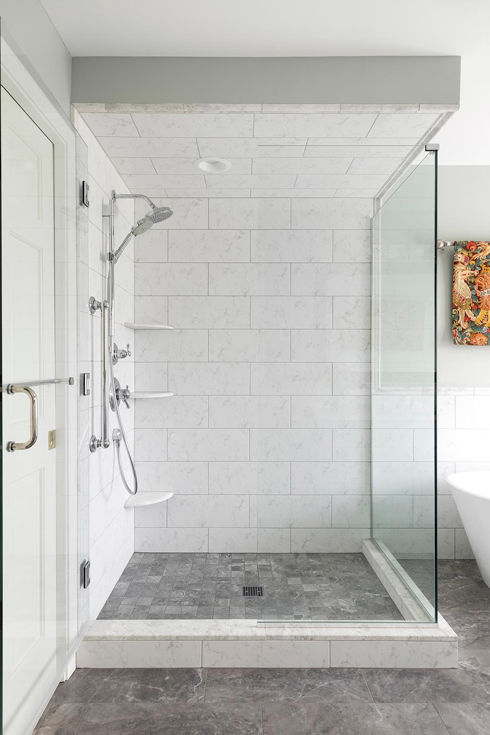 accessible shower with white and grey tile