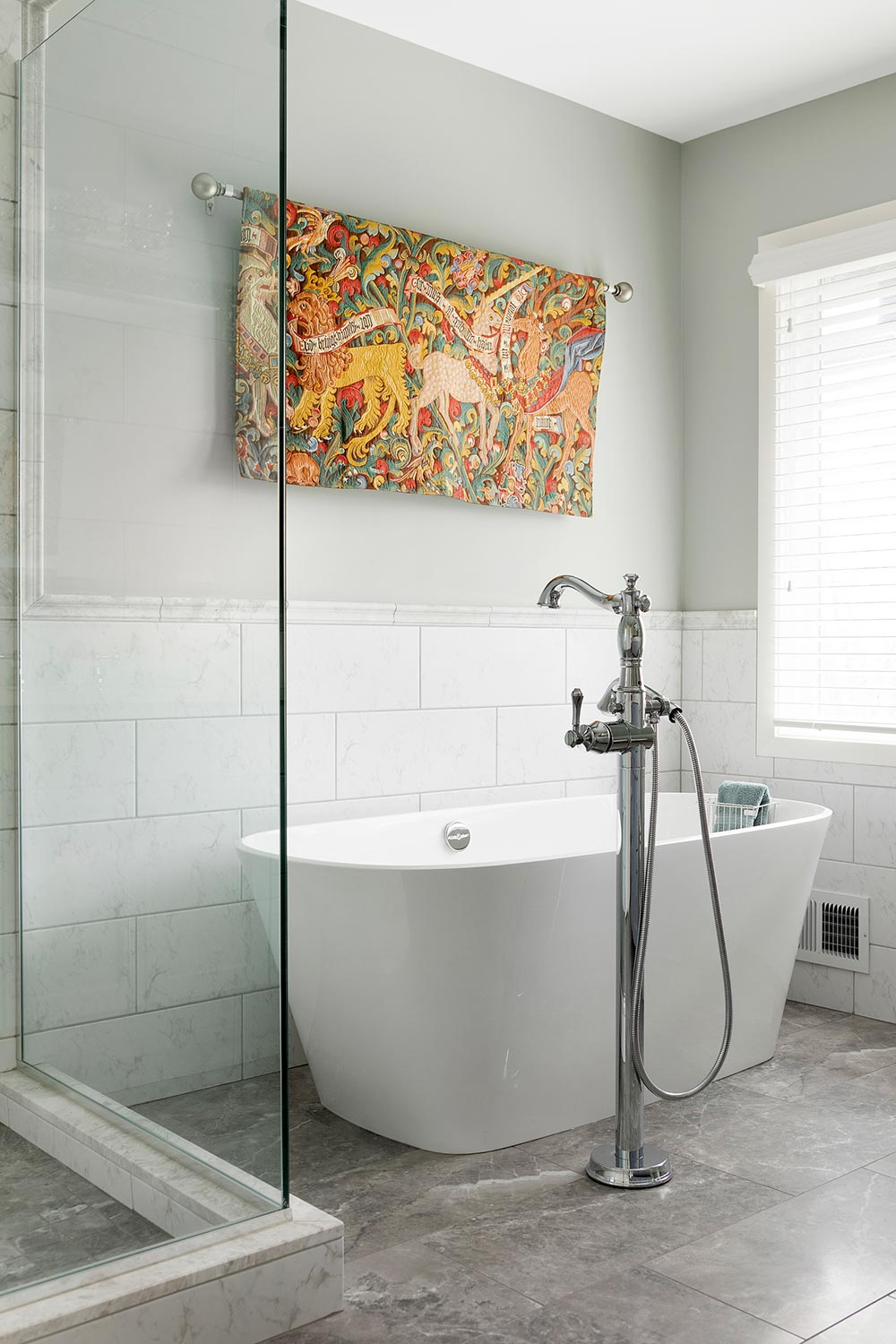 Large freestanding tub below a tapestry wall hanging