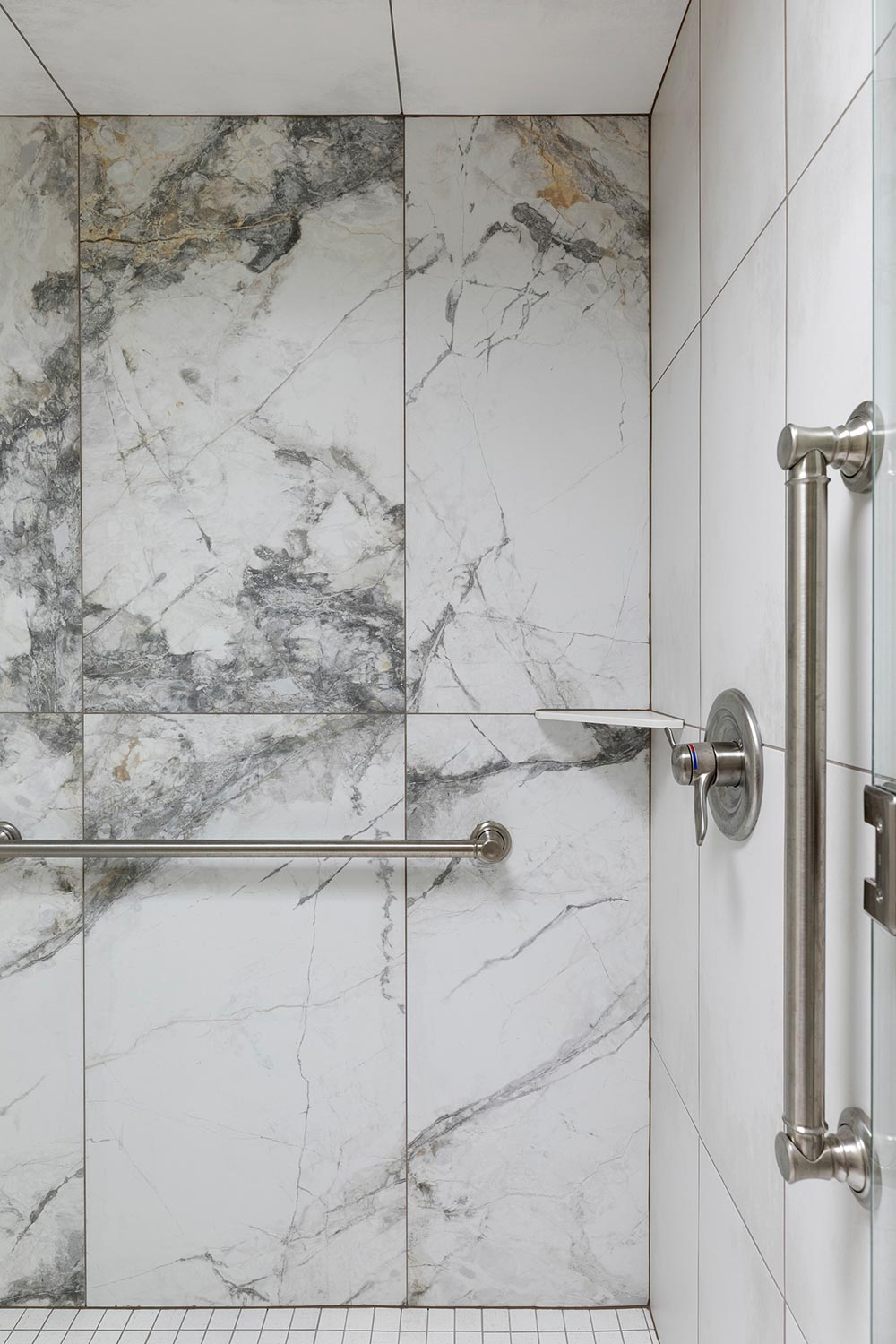 Tiled focal wall in accessible design shower with grab bars